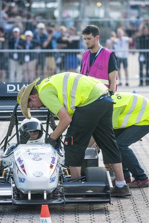 safety check: HOCKENHEIM, GERMANY - AUGUST 2, 2015: Officials and Scruitineers check the safety and regulations of the Formula Student Team Delft (TU Delft)'s car, prior to their start of the dynamic endurance event of the officious world championships