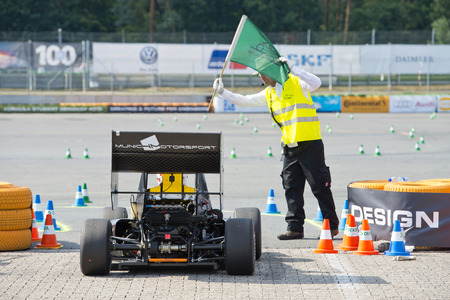 world championships: HOCKENHEIM, GERMANY - AUGUST 1, 2015: Formula Student Team Munich Motorsports gets a green flag from a marshall to start in te endurance race of the officious world championships Formula Student Germany at the Hockenheim ring