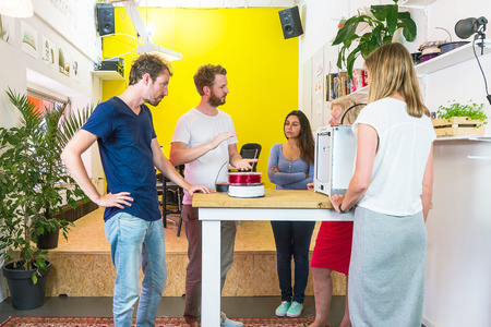 rapid prototyping: Designers, standing around a table with a 3D printer discussing novel process improvement in product development in a creative design studio