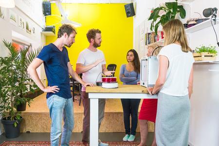 Ontwerpers, die zich rond een tafel met een 3D-printer bespreken roman procesverbetering in productontwikkeling op een creatieve design studio
