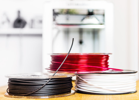 industrial design: Three spools, or coils, of biodegradable polymers, used for 3D printers to create lithographical products Stock Photo