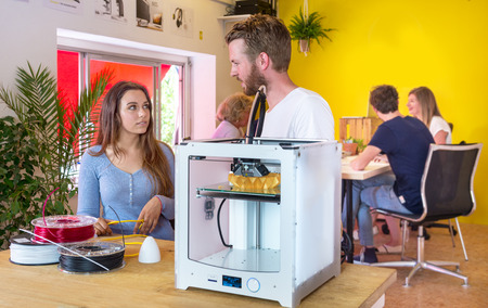 Designers standing behind a 3D printer, surrounded with coils of biodegradable polymer, waiting for a product concept to be printed in the printer. Other engineers working togegher in the background