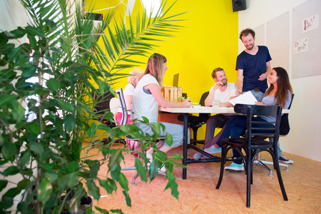 environment: Designers, sitting in at a large table in a creative environment and office, surrounded by tack boards with drawings, plants and a bright yellow wall Stock Photo