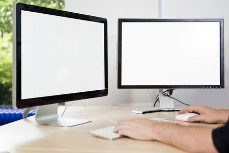 Two computer monitors with a white screen on a desk, with a man's hands on a keyboard in an office, suited for mock-ups and presentations, with plenty of copy space for your designs