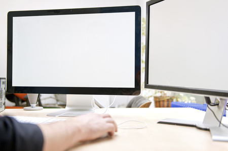 computer screens: Two large computer screens on a desk, to be used for presentations and mock ups. A computer expert has his hands on the keyboard