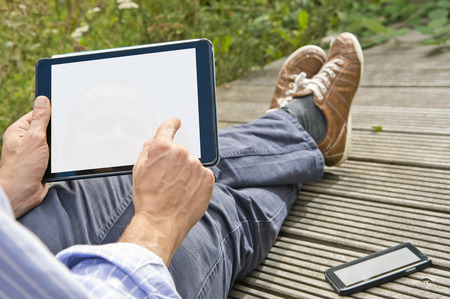 Man, tapping on a tablet, playing a game outdoors, sitting on a plank bridge, whith his phone next to him. Both can be used as presentation for mock-up apps, website and presentations. Stock Photo