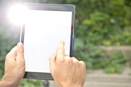 replaced: Man, tapping on a tablet outdoors. The tablet screen is white, to be replaced by your app, website or product
