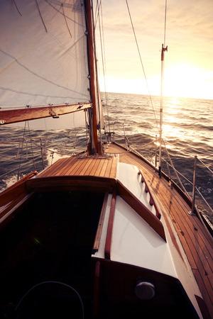 Classic sailing yacht sails towards the setting sun