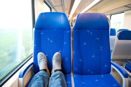 compartments: Two feet resting on the opposite seats in an empty train coach, traveling alone