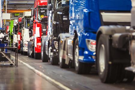 Rij van gloednieuwe, glanzend, vrachtwagens in diverse kleuren, klaar om af te komen van een productielijn in een vrachtwagen fabriek