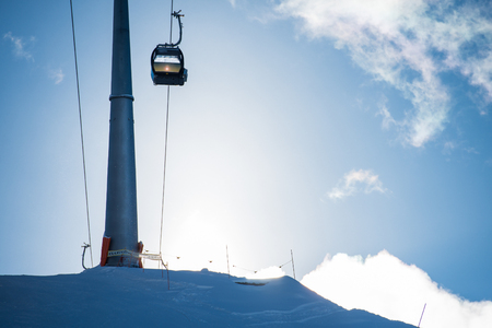 wintersport: Ski lift or telecabine in a ski resort on a slope, covered with snow during wintersport season, with the sun rising over the mountain