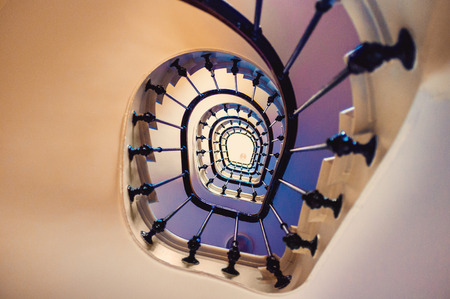 steps and staircases: Asymmetric spiral staircase leading up several floors in an old building, looking up.