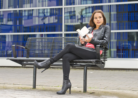 distraction: Pretty woman on her break, sitting on a bench in an urban environment, gets distracted from the book shes reading