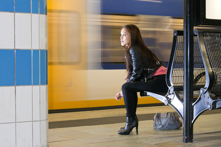 public transport: Woman, sitting on a bench, with her purse on the platform next to her, looking at a passing train, waiting. Stock Photo