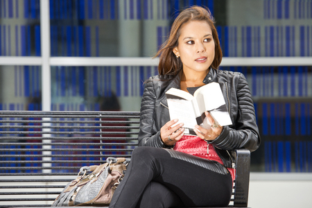 eye contact: Woman, siting on a bench, outside, being distracted and making eye contact with a stranger Stock Photo