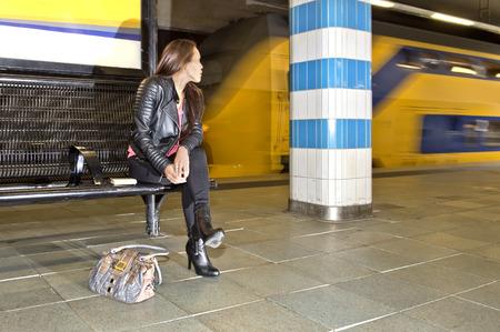 personas sentadas: Mujer que mira sobre su hombro a un tren que pasa en una estación de tren subterráneo, sentado en un banco, con un libro a su lado y un bolso en el suelo de la plataforma