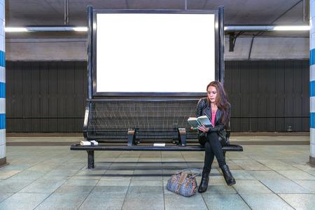下に、本を読んでベンチに座っている女性と地下駅でブランクの看板