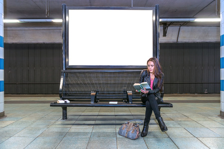 A blank billboard at an underground railway station with a woman sitting on a bench underneath, reading a book