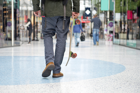 waist down: Guy from the waist down with a skateboard, walking casually through a modern shopping mall Stock Photo