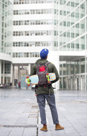 disctrict: Skateboarder, with his skateboard tucked away in his backpack, looking at a tall, modern, office building