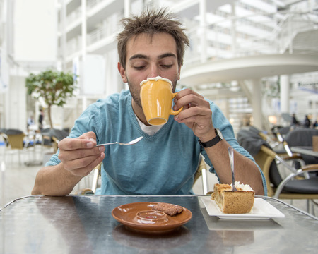 gratifying: Young man enjoying hot chocolate with whipped cream and an apple pie on a terrace in a shopping mall