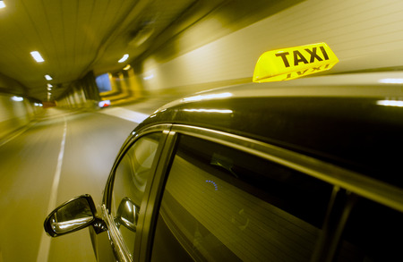 taxi sign: A black taxi, driving through a dunnel, with the taxi sign lit, apporaching a junction and exit ramp