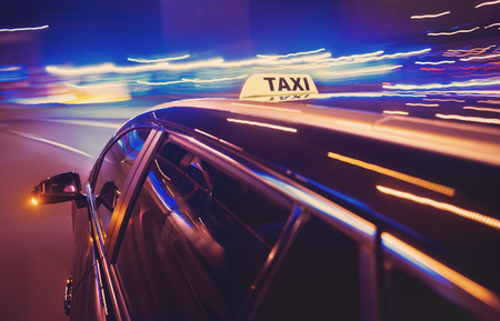 taxi sign: Taxi taking a left turn at night in an urban surrounding, seen from the rear end of the cab
