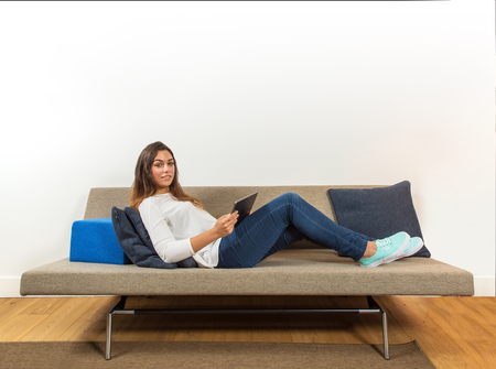 Young woman, holding an electronic, portable, tablet, lying on a stylish couch, looking into the camera, with plenty of copy space Stock Photo