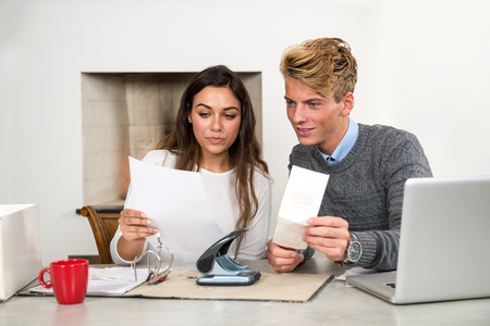 Young couple, comparing, filing and sorting out their personal finance situation, paying bills, and archiving tax return forms, using a ring binder and a laptop, comparing and balancing their checkings account