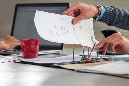 Mensen, beboeten documenten en het doen van de administratie, werken op een laptop en archiveren van facturen en rekeningen in een ringband, archiveren voor belastingaangiften
