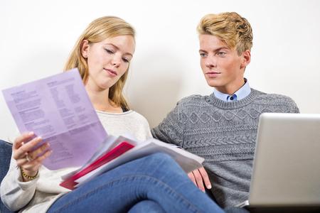 chequera: Pareja de jóvenes sentados uno junto al otro, pasando por las facturas, facturas y otros documentos, equilibrar su chequera en un ordenador portátil