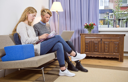 personal finance: Young couple, sitting on a couch with a laptop and stack of bills, taking care of their personal finance and administration