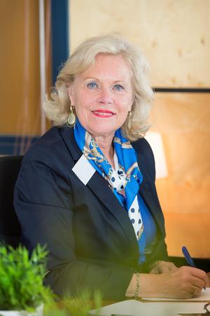 mujeres ancianas: Con experiencia, la reintegración de la mujer como recepcionista tomando notas en hojas de papel detrás del mostrador de la oficina delante de una gran empresa