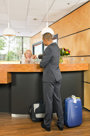 and carry on: Business class passenger, with carry on luggage and priority airport labels checking in at a hotel, handing over his passport to the senior receptionist behind the counter Stock Photo