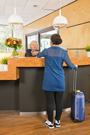and carry on: young woman, with a carry on suitcase next to her, handing over her passport, registering, during checkin at a hotel, where a senior receptionist provides customer service Stock Photo