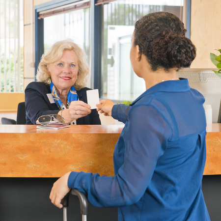 visitors: File name:     Receptionist helping a guest at a hotel, handing out the electronic key card for their room