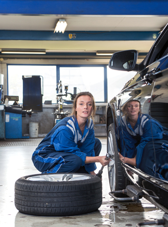 compound: Female mechanic, loosening bolts, to change the tyres on a vehicle for winter and all weather profile tyres