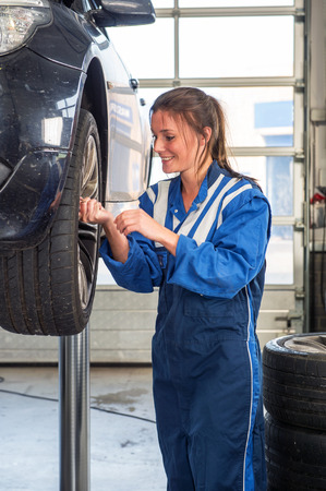 car lift: Young female mechanic, removing the bolts of the front wheel of a vehicle on a car lift, wearing coveralls, replaicng tyres Stock Photo