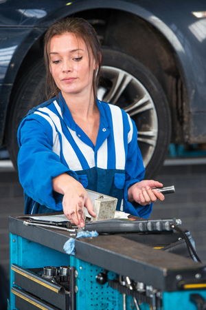 car lift: Young woman mechanic, reaching for a torque wrench on a tool trolley in front of a vehicle on a car lift with the car she's working on