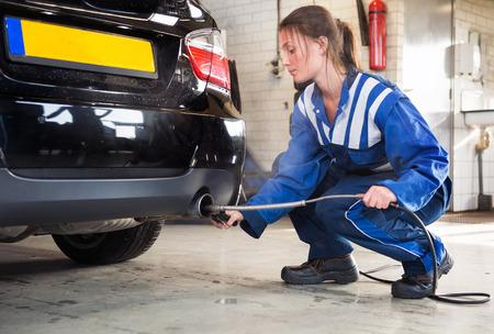 mécanicien Femme sonder un capteur dans l'échappement d'une voiture, en mesurant les niveaux de dioxyde de carbone et des fumées d'émission des valeurs d'une voiture diesel alimenté Banque d'images