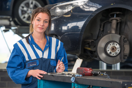 mot: Female mechanic checking a car during a periodic technical service or MOT test,