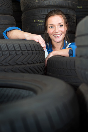 treads: Young, pretty, mechanic, surrounded by stacks of car tyres with varous treads, sizes and compounds, smiling Stock Photo