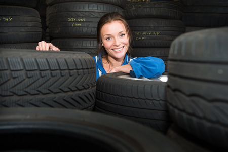 treads: Portrait of a young, pretty, mechanic in a store room, surrounded by tyres with various treads, and purposes
