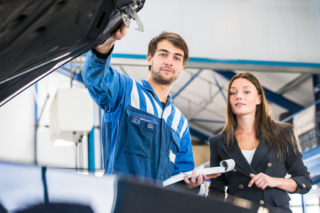 hood: Mechanic, taking a look under the hood of a business woman's car with an order form and pen in his hand, assessing the work needed to fix her car