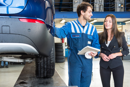 A friendly mechanic providing customer service to a young business woman, showing her the work he's done on her car, equipped with a new set of winter tires to ensure road safety. Standard-Bild