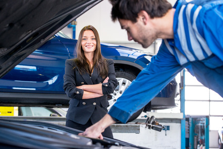 happy customer: Young, pretty businesswoman looks happily at  the mechanic, whilst he's fixing her car in a garage, aimed at customer service and instant assistance