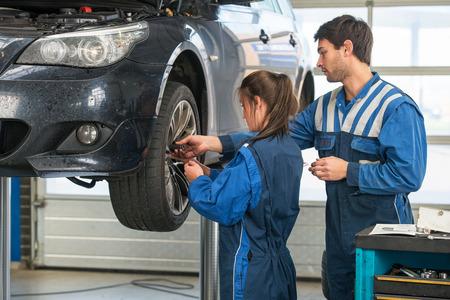 best practices: Mechanic teaching an intern the best practice. Learning on the job during a practical internship in a garage