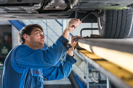 mechanics: Mechanic, examining the suspension of a vehicle with a steel rod for any undesired clearances as part of a periodical vehicle safety inspection or mot test