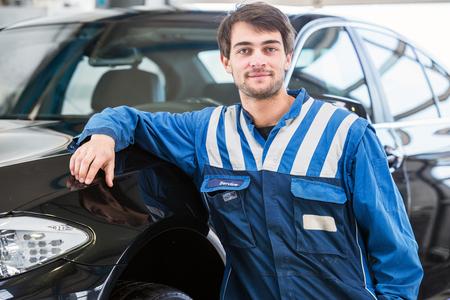 proficient: A confident, reliable, trustworthy looking professional mechanic, leaning against a black sedan