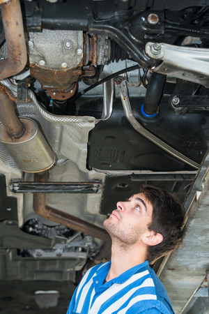 exhaust system: Mechanic examining the exhaust system of a car, underneath the vehicle during a MOT test or periodic maintenance inspection Stock Photo
